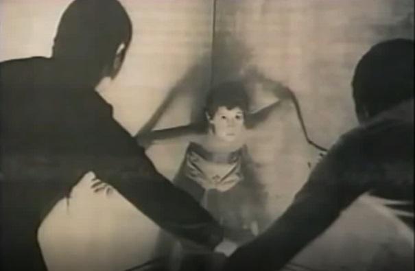 Nambla - Pokazuje przerażonego chłopca zagonionego w kąt przez dwóch dorosłych mężczyzn